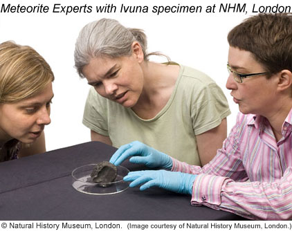 Curator Caroline Smith (right) pointing to the Ivuna meteorite along with Dr. Sara Russell (left) and Dr. Gretchen Benedix (center). Copyright by the Natural History Museum London. Click for more information.